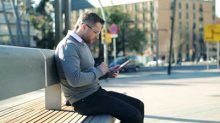stock-footage-young-man-with-tablet-computer-sitting-on-bench-in-the-city